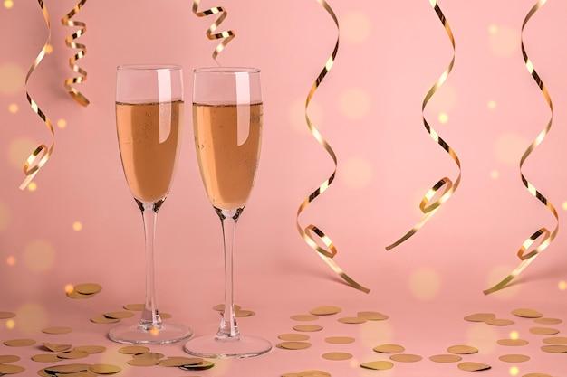 Twee glazen champagne op delicaat roze met gouden bokeh en serpentijn.