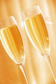 Twee glazen champagne tegen gouden achtergrond
