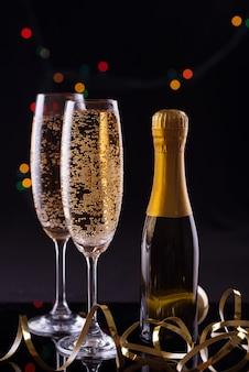 Twee glazen champagne tegen wazig kerstverlichting. ondiepe scherptediepte.