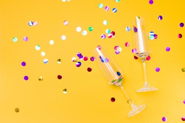 Twee glazen champagneglazen op een gele achtergrond bezaaid met confetti, glanzende cirkels in de glazen kopie plaats