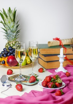 Twee glazen champaigne op witte houten tafel met vintage boeken en klok, verschillende tropische vruchten en aardbeien