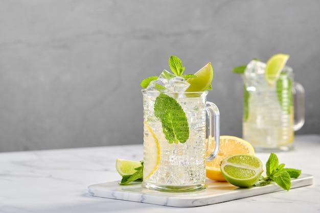 Twee glazen citroen, limoen en munt koude limonade op marmeren tafel