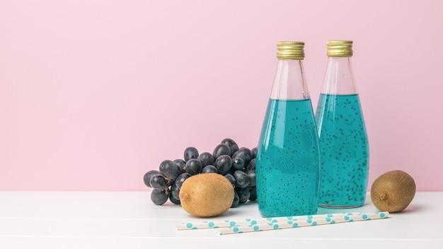 Twee glazen cocktailflessen en druiven op een roze oppervlak