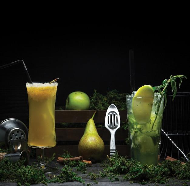 Twee glazen cocktails gemaakt van citroen, munt en peer, groene appel
