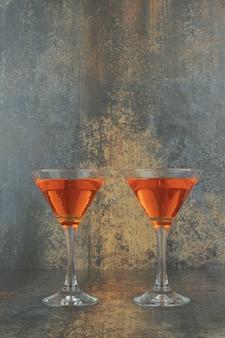 Twee glazen cocktails op marmeren tafel.
