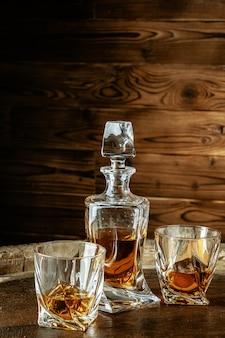 Twee glazen cognac of fles en fles op de houten tafel