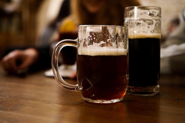 Twee glazen donker bier op een houten tafel