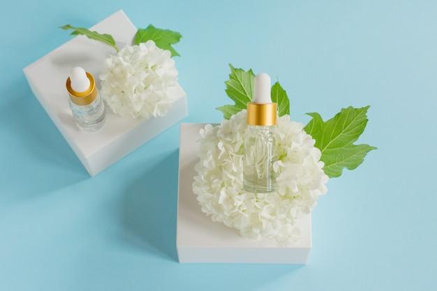 Twee glazen druppelflesjes voor medisch en cosmetisch gebruik en witte tedere bloesembloemen op een lichtblauwe achtergrond. huidverzorging en spa-concept.