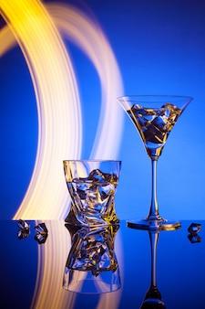 Twee glazen een cocktail martini whisky-ijs, tegen het blauw van prachtige lichteffecten.
