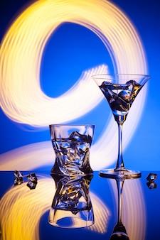 Twee glazen een cocktailijs, tegen het blauw van prachtige lichteffecten.