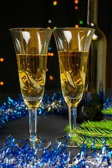 Twee glazen en een fles wijn. kerstmis en nieuwjaar concept op zwarte achtergrond.