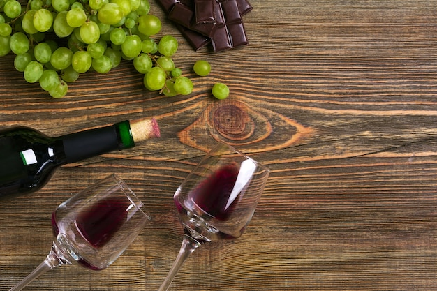 Twee glazen, fles rode wijn en druif op een houten tafel. bovenaanzicht. ruimte kopiëren. plat leggen. stilleven