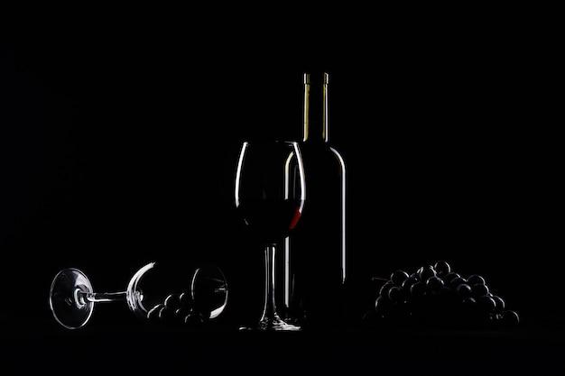 Twee glazen, fles wijn en druiven op zwarte achtergrond