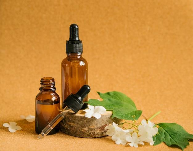Twee glazen flessen cosmetische olie staan op een stuk hout. alternatieve geneeswijzen en aromatherapie.