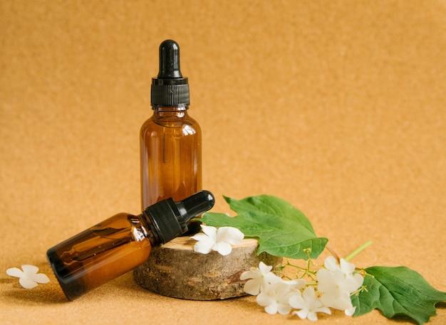 Twee glazen flessen cosmetische olie staan op een stuk hout. in de buurt zijn kleine witte bloemen.