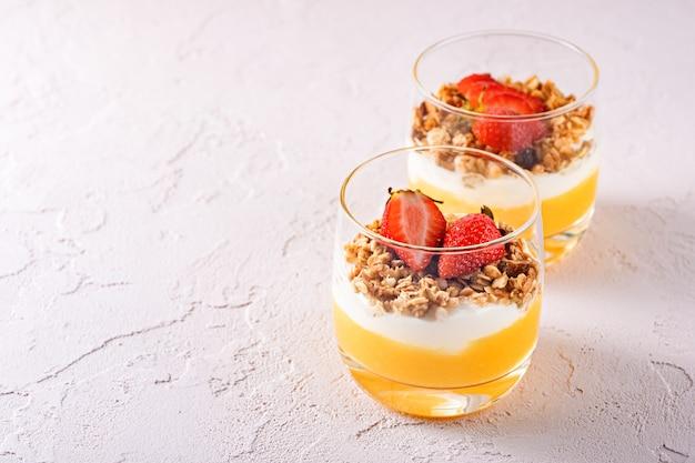 Twee glazen glazen met vegetarische desserts gemaakt van mango smoothie, griekse yoghurt, granola en aardbei