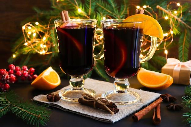 Twee glazen glühwein, kaneel en sinaasappels op feestelijke kerstmis
