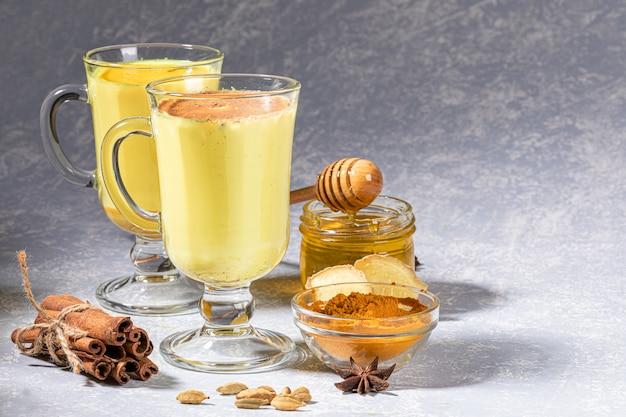 Twee glazen glühwein met gouden melk met ingrediënten op lichtgrijze achtergrond.