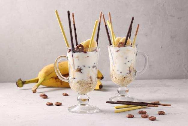 Twee glazen granola met chocolade en banaan, versierd met stokjes pocky op grijze achtergrond, horizontaal formaat