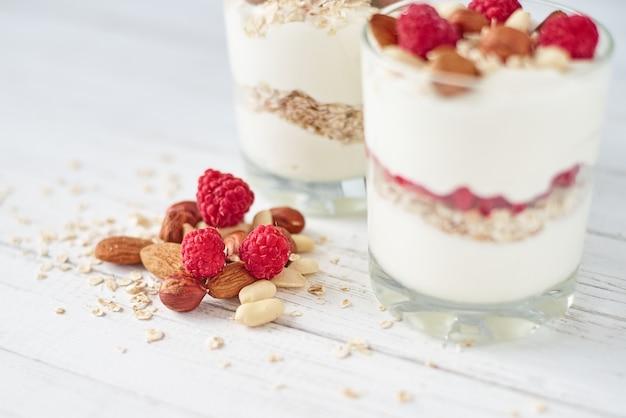 Twee glazen griekse yoghurtgranola met frambozen, havermoutvlokken en noten