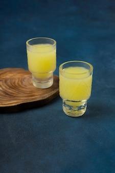 Twee glazen heerlijke limoncello met een standaard op een blauwe achtergrond