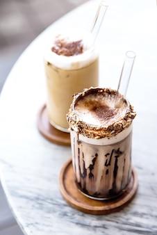Twee glazen iced latte op marmeren achtergrond. zomerse drankjes.