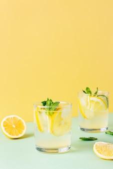Twee glazen ijscitroenwater met muntblaadjes op een gele en groene achtergrond. frisse zomerdrank met frisdrank.