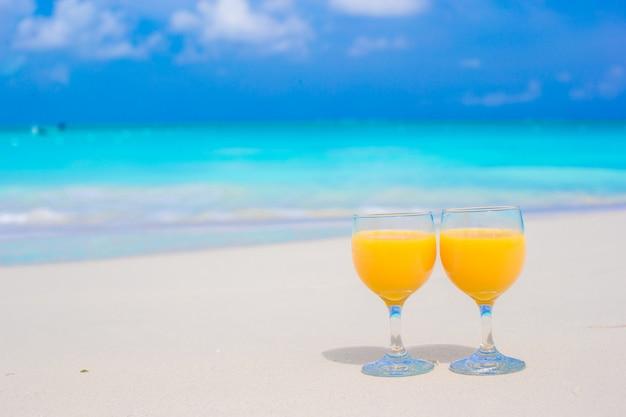 Twee glazen jus d'orange op tropisch wit strand