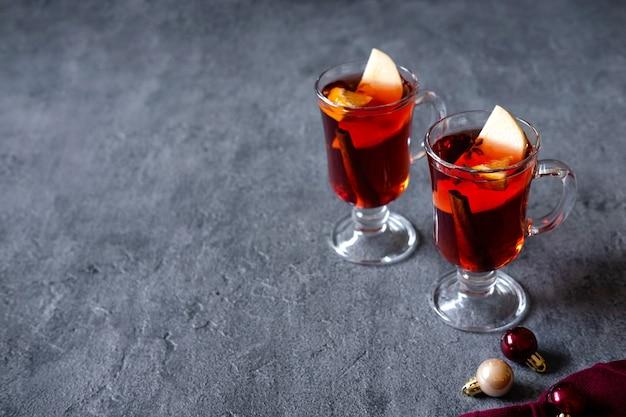 Twee glazen kerst glühwein met sinaasappels en kruiden.