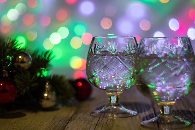 Twee glazen kerstchampagne met kerstboom versierd met rode en zilveren ballen tegen lichte bokeh achtergrond.