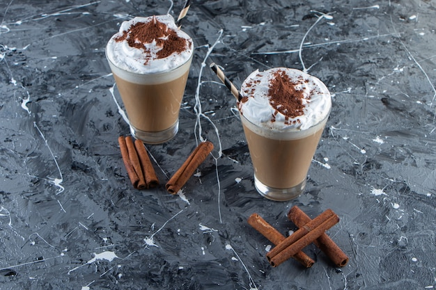 Twee glazen koffie met slagroom op marmeren oppervlak.