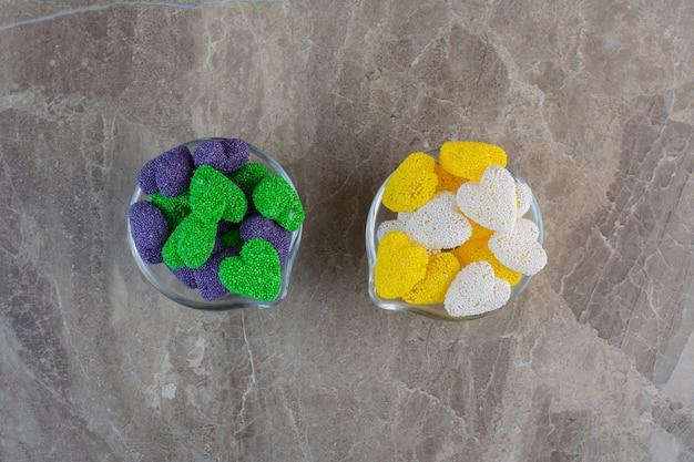 Twee glazen kom vol met kleurrijke snoepjes op grijze ondergrond.
