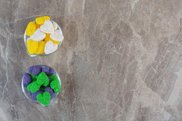 Twee glazen kom vol met met kleurrijke snoepjes.