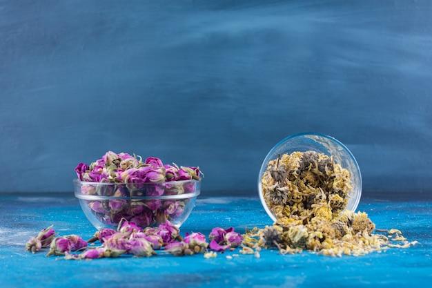 Twee glazen kommen met gedroogde bloemen op blauwe tafel.