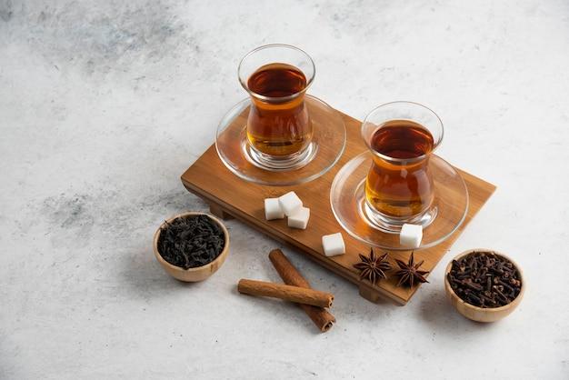 Twee glazen kopje thee met suiker en steranijs.