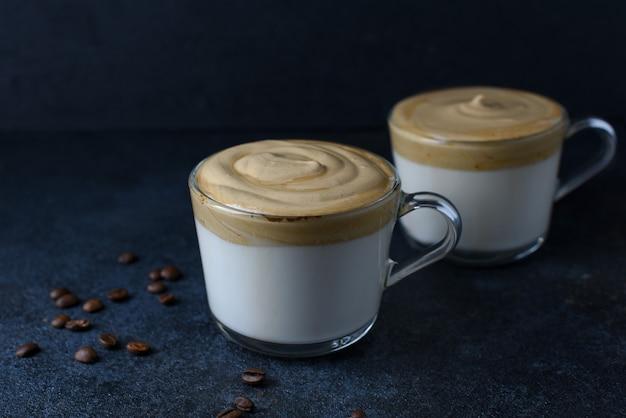 Twee glazen kopjes dalgona koffie versierd met koffiebonen op donkere achtergrond