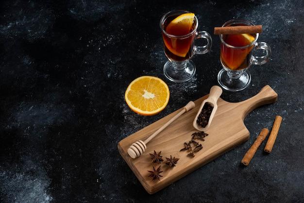 Twee glazen kopjes thee en met kaneelstokjes en houten lepel.
