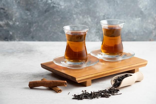 Twee glazen kopjes thee met kaneelstokjes en losse thee. foto van hoge kwaliteit