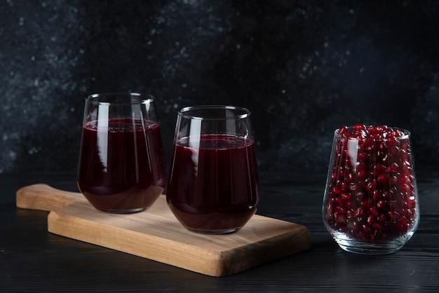Twee glazen kopjes vers granaatappelsap op een houten bord.