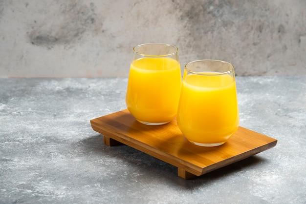 Twee glazen kopjes vers sinaasappelsap op een houten bord.