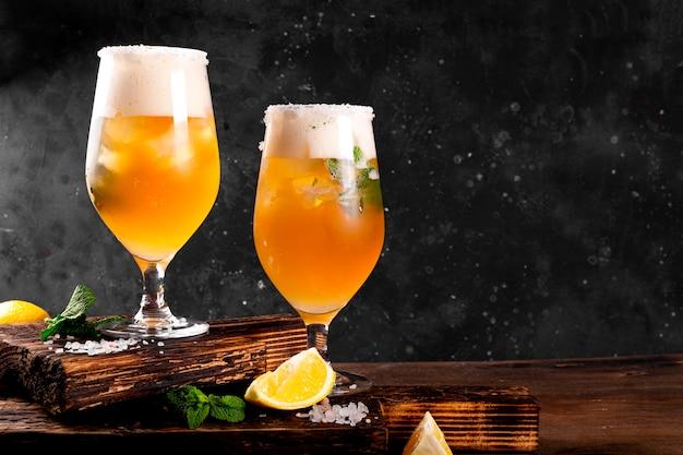 Twee glazen koud bier met citroen en munt traditionele latijns-amerikaanse drank michelada op donker mi