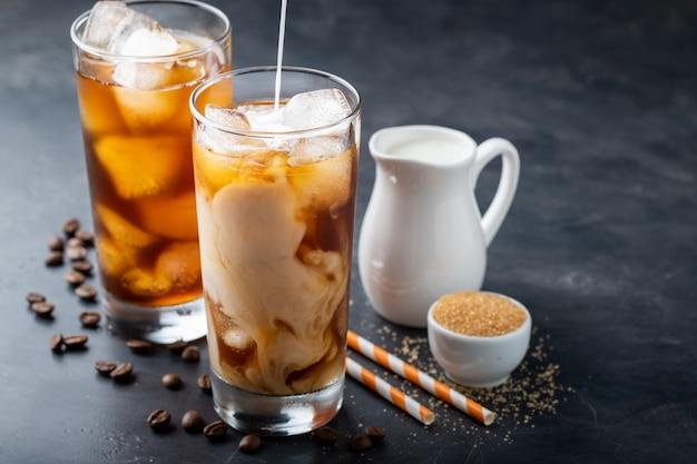 Twee glazen koude koffie op een donkere achtergrond.