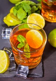 Twee glazen koude verfrissing thee met ijs en citroen fruit.