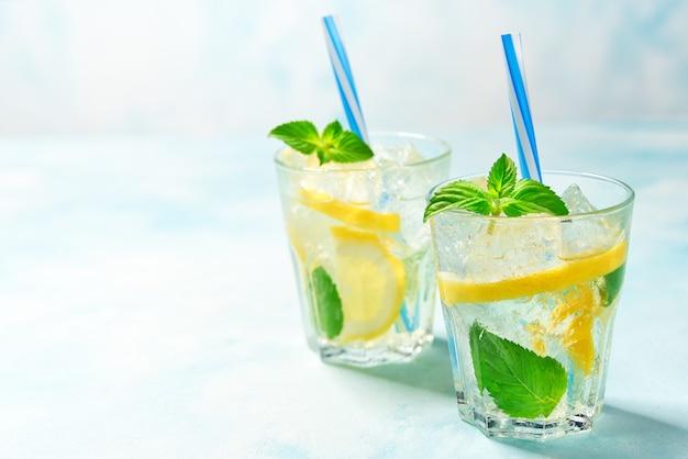 Twee glazen limonade met verse citroen op turkooise achtergrond, met exemplaarruimte