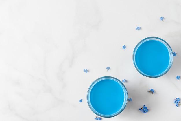 Twee glazen met blauwe matcha latte en vergeet me niet bloemen op witte tafel