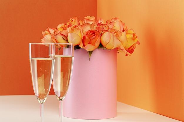 Twee glazen met champagne en en boeket rozen