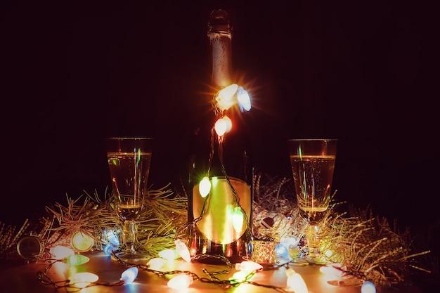 Twee glazen met champagne en fles op een houten tafel versierd met kerstaccessoires om het nieuwe jaar en kerstmis te vieren. romantische avond. de gloed van de slingers. valentijnsdag