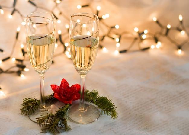 Twee glazen met champagne en kerstverlichting kaart met ruimte om te schrijven