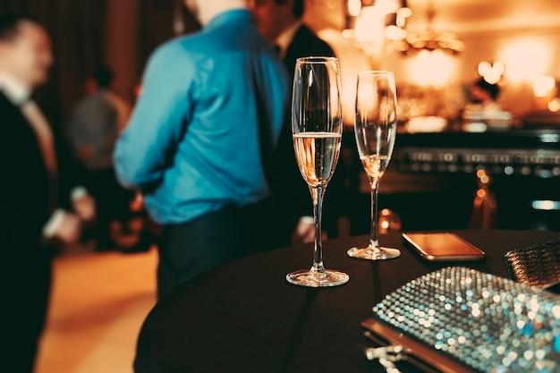 Twee glazen met champagne, glanzende dameshandtas en een telefoon op tafel
