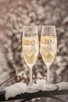 Twee glazen met champagne op de sneeuw